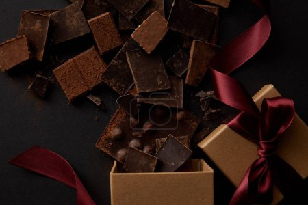 top view of gift boxes and delicious chocolate pieces on black