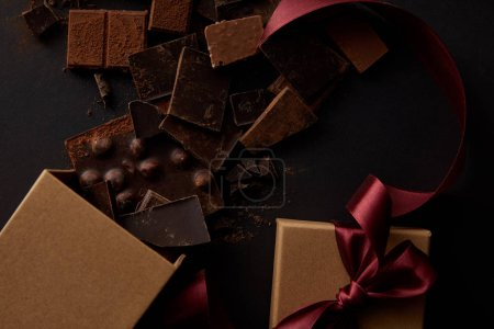 top view of gourmet chocolate pieces with nuts and gift box on black