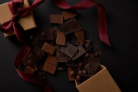 top view of delicious chocolate pieces with nuts and gift box on black