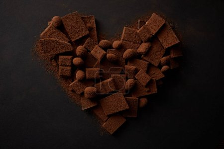 Photo for Top view of tasty chocolate with nuts and cocoa powder arranged in shape of heart on black - Royalty Free Image