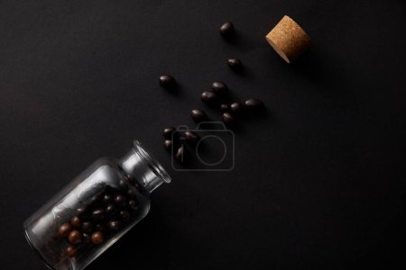 top view of gourmet chocolate balls, glass jar and cork on black