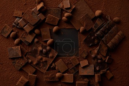 top view of chocolate pieces with nuts and cocoa powder on dark background
