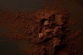 top view of delicious chocolate pieces and gourmet cocoa powder on dark background