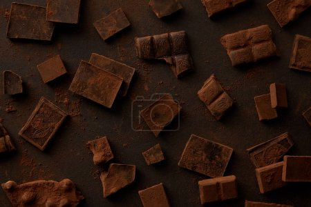 Photo for Top view of delicious chocolate pieces on black background - Royalty Free Image