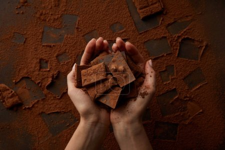 cropped shot of delicious chocolate pieces in human hands