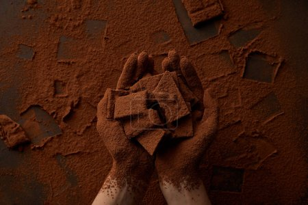 partial view of person holding chocolate pieces and cocoa powder
