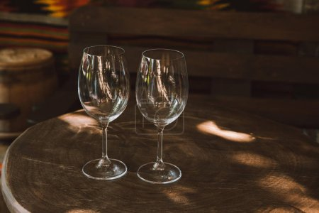 close-up shot of glasses for wine on rustic wooden table