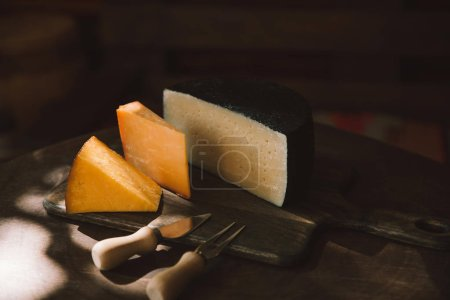 various sorts of cheese and cutlery on rustic wooden table