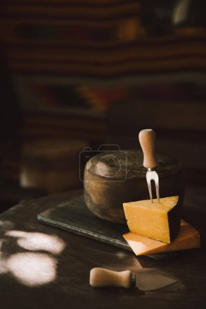 two sorts of cheese slices with fork on rustic wooden table