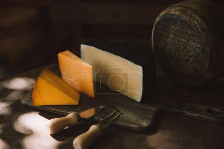 various sorts of delicious cheese with cheese cutlery on rustic wooden table