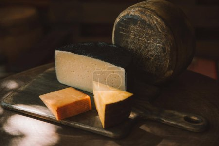 various sorts of delicious cheese on rustic wooden table