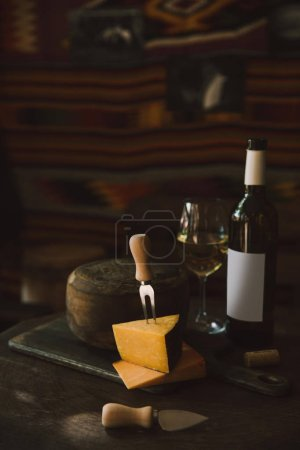 sliced cheese with white wine on rustic wooden table