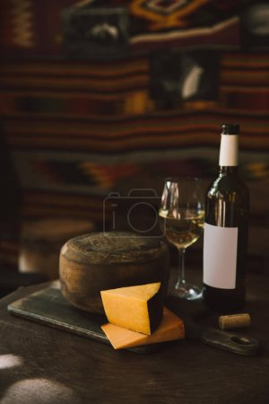 delicacy cheese with white wine on rustic wooden table