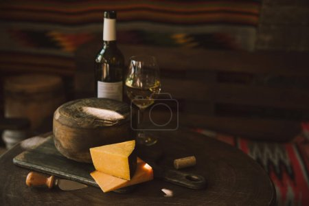 delicious cheese with white wine on rustic wooden table