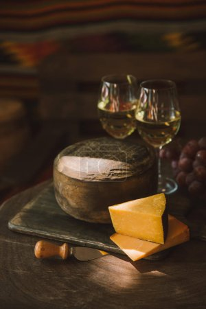 sliced delicious cheese with wine and grapes on wooden cutting board