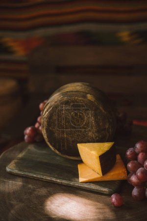 close-up shot of cheese head on cutting board with grapes