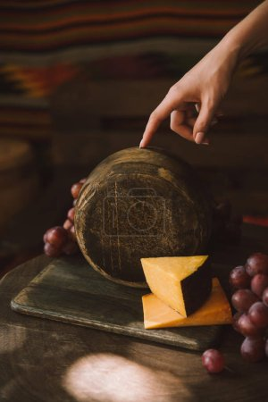cropped shot of woman holding cheese head on cutting board with grapes
