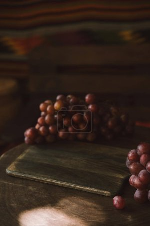 close-up shot of red grapes on rustic wooden table