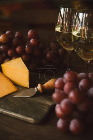 close-up shot of sliced cheese with knife, grapes and white wine on cutting board