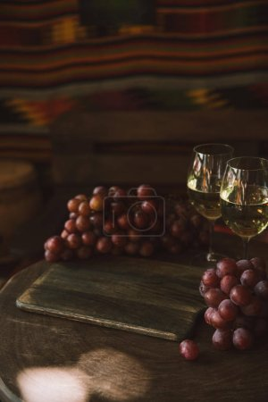 close-up shot of glasses of white wine and grapes on rustic wooden table