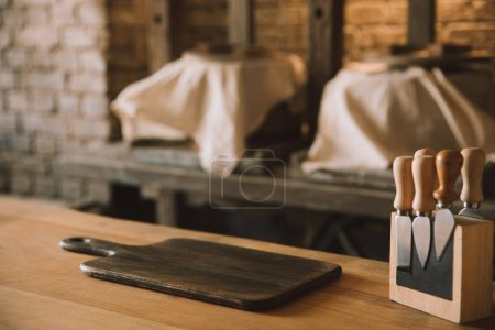 Photo for Empty cutting board with cheese knives on stand on wooden table at cheese manufacture - Royalty Free Image