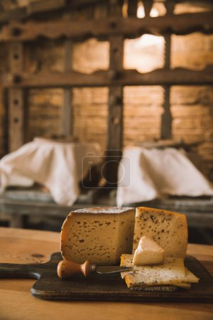 Photo for Delicious sliced cheese with knife on wooden cutting board - Royalty Free Image