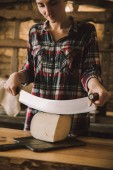 young woman cutting cheese with double handled knife