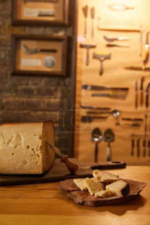 close-up shot of sliced cheese with knife on wooden boards