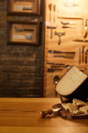Photo for Close-up shot of sliced cheese with knife on wooden cutting board - Royalty Free Image