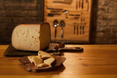 Close-up shot of sliced cheese on wooden cutting b...