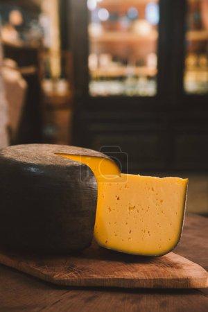 Photo pour Délicatesse, tranché de fromage sur planche à découper en bois rustique en fromagerie - image libre de droit