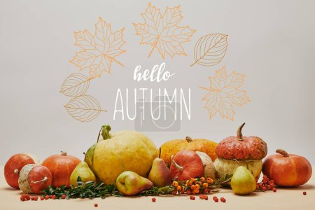 Photo for Autumnal decoration with pumpkins, firethorn berries and ripe yummy pears on tabletop with HELLO AUTUMN lettering - Royalty Free Image