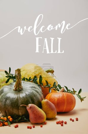 Photo for Autumnal decoration with pumpkins, firethorn berries and ripe yummy pears on tabletop with WELCOME FALL lettering - Royalty Free Image