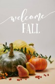 autumnal decoration with pumpkins, firethorn berries and ripe yummy pears on tabletop with WELCOME FALL lettering