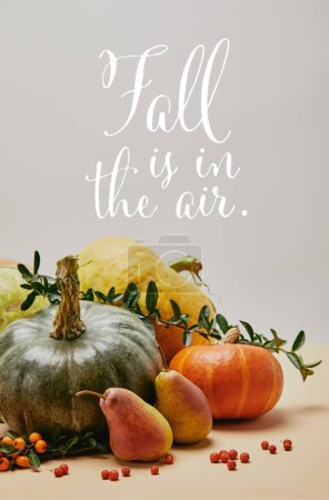 Photo for Autumnal decoration with pumpkins, firethorn berries and ripe yummy pears on tabletop with FALL IS IN THE AIR lettering - Royalty Free Image