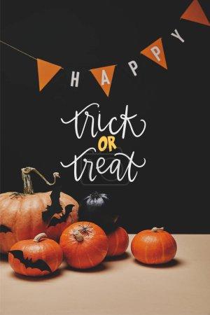 """Photo pour Citrouilles, chauves-souris en papier et guirlande de papier avec mot heureux et avec lettrage halloween """"trick or treat"""" - image libre de droit"""