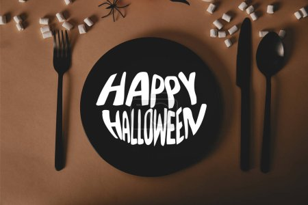 "top view of black plate with ""happy halloween"" lettering, fork and knife with marshmallows on table"