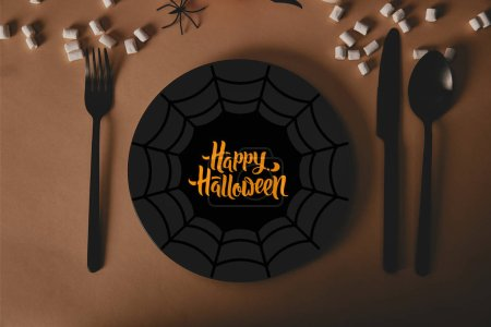 """top view of black plate with spider web and """"happy halloween"""" lettering, fork and knife with marshmallows on table"""