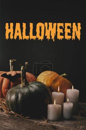 citrouilles, chauve-souris de papier noir et bougies sur table avec l'inscription «halloween»