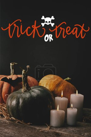 "pumpkins, black paper bat and candles on table with skull and ""trick or treat"" halloween lettering"