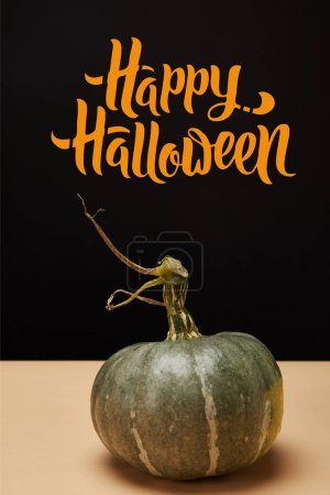 "one green pumpkin on table with ""happy halloween"" lettering"