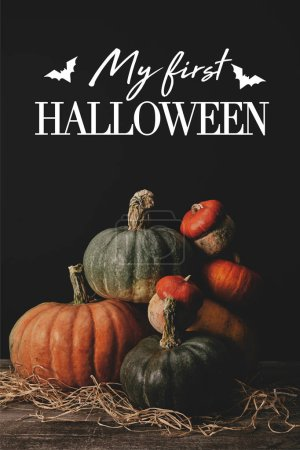 """pile of ripe pumpkins on table with bats and """"my first halloween"""" lettering"""
