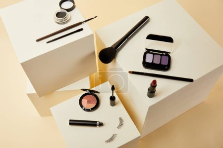 high angle view of various makeup accessories on beige cubes