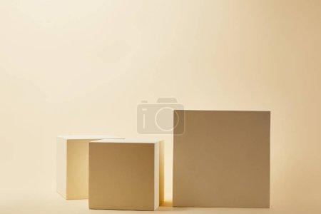 nature morte de cubes de différentes tailles sur surface beige