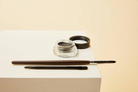 Photo pour Gros plan des ombres à sourcils peut avec des brosses sur cube beige - image libre de droit