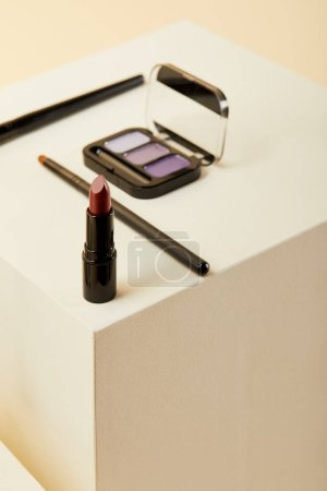 close-up shot of lipstick with purple eyeshadows case and brushes on beige