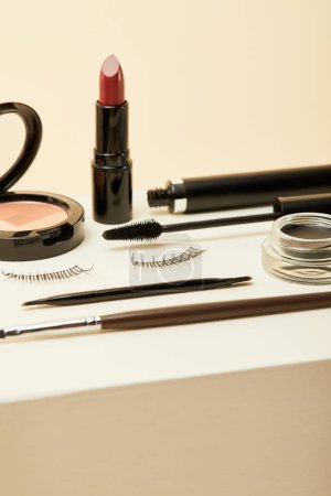close-up shot of various makeup accessories on beige