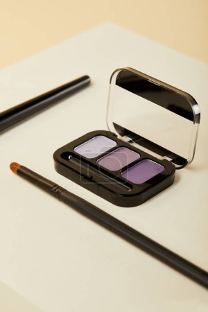 close-up shot of purple eyeshadows case with brush on beige