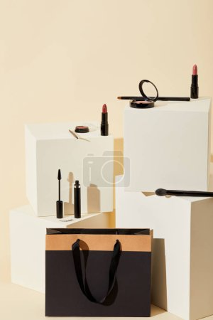 various makeup supplies lying on beige cubes with paper bag