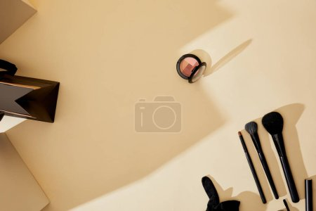 top view of makeup supplies lying on beige tabletop